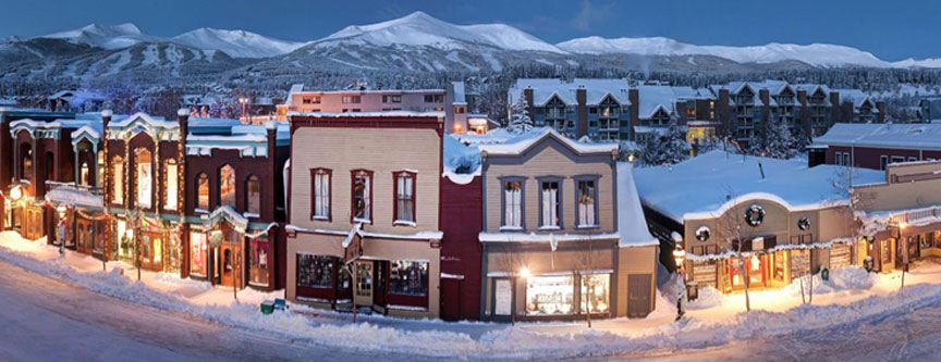 Main Street Breckenridge, illuminated by lights and store fronts reflect the 1880's charm of yesteryear while the ski resort accents the background.