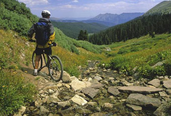 A mountain biker surveys the trail while riding near Breckenridge.
