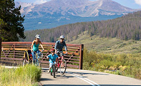 A family bikes on the trail between Breckenridge and Frisco in Summit County, Colorado