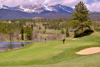 Breckenridge ski resort rises imperiously in the background as a golfer lines up his putt.